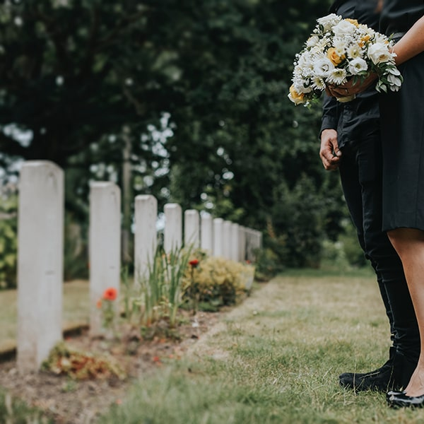 couple-standing-together-by-a-gravestone-min